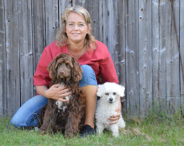kvinna sitter mot lada med två hundar